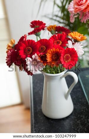 bouquet of gerberas in vase in the interior. Vertical view - stock photo
