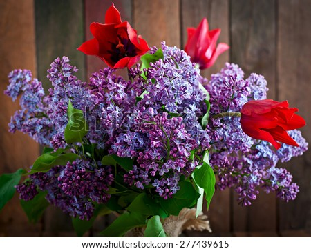 Bouquet of lilac and tulips on a wooden background - stock photo