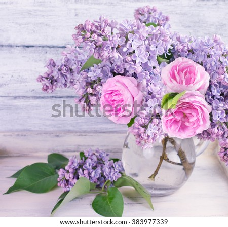 Bouquet of lilac flowers and roses in glass bottle on shabby wooden board - stock photo