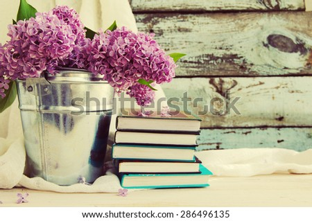 Bouquet of lilac flowers in a metal bucket and a pile of books against an old wooden board, a decor in vintage style - stock photo