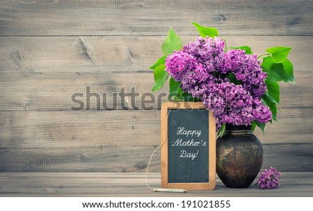 bouquet of lilac flowers in vase on wooden background. blackboard with sample text Happy Mother's Day! retro style toned picture - stock photo
