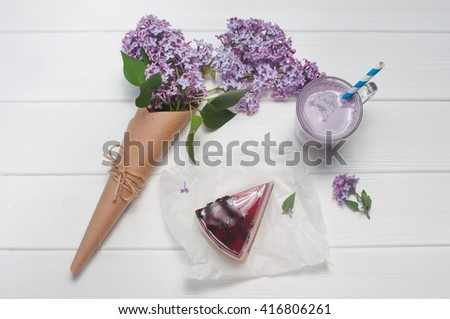 Bouquet of lilac flowers near black current cheesecake slice and bilberry milkshake on the white wooden background. Top view. - stock photo