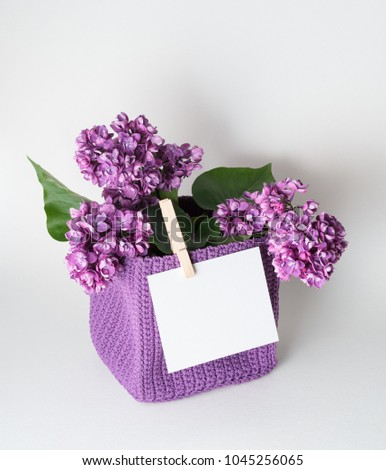 Bouquet of lilac with a greeting card. Blank white sheet with space for text