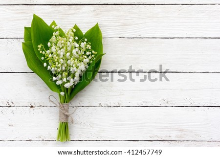 bouquet of lilies of the valley flowers with green leaves tied with twine in the water droplets on the white wooden boards. with space for posting information - stock photo