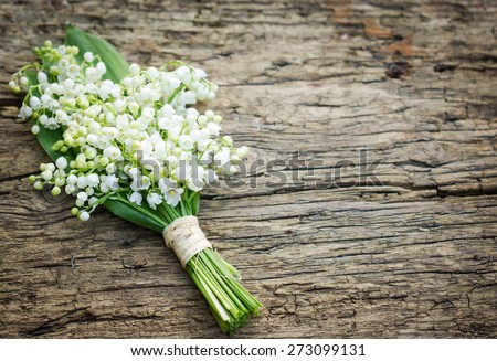Bouquet of lilies of the valley on the wooden board - stock photo