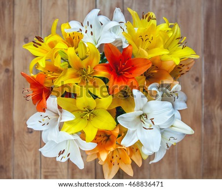 bouquet of multicolored lilies on a wooden background , top view