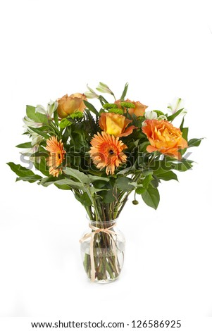 Bouquet of orange daisies  and carnation in a crystal jar tied with ribbon - stock photo