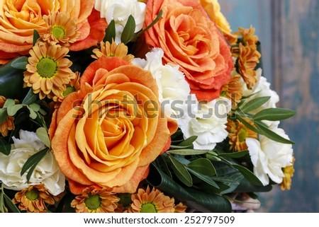 Bouquet of orange roses and ivory carnation flowers - stock photo