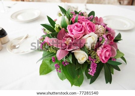Bouquet of orchid flowers and tulips on arranged table - stock photo