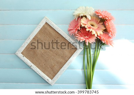 Bouquet of pink and white gerberas with frame on blue wooden background - stock photo