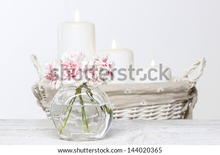 Bouquet of pink carnations in small glass vase. White candles in wicker basket in the background. - stock photo