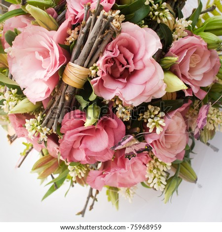 bouquet of pink flowers decorated with leaves and small branches