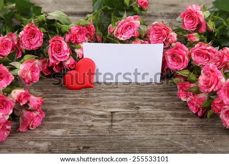 Bouquet of pink roses, heart  and greeting card on a wooden background - stock photo