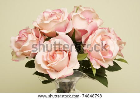 Bouquet of pink roses in a glass vase against a light green background. - stock photo