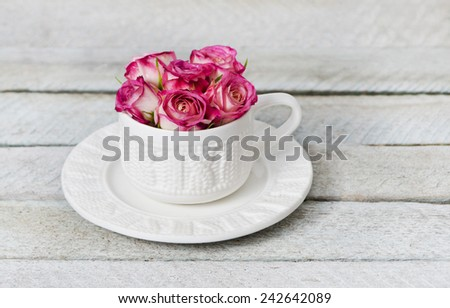 bouquet of pink roses in a white cup on a old wooden panel - stock photo