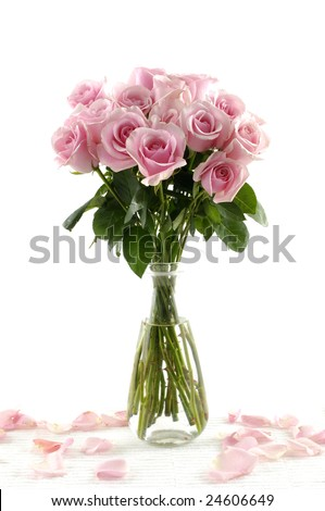 Bouquet of pink roses in glass vase with petals isolated on white - stock photo