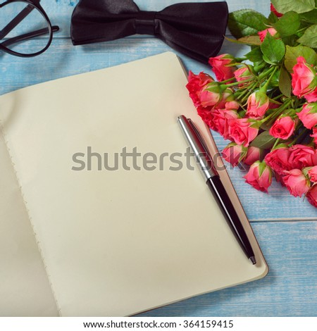 Bouquet of pink roses with an open notebook with blank pages and gift closeup. Square frame - stock photo