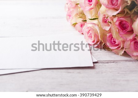 Bouquet of pink roses with blue ribbon for present on a vintage wooden background, copy space, closeup - stock photo