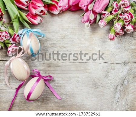 Bouquet of pink tulips and easter eggs on wooden background. Copy space - stock photo
