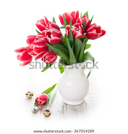Bouquet of pink tulips in vase and quail eggs on the white background with copy space for text. Easter concept. - stock photo