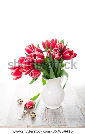 Bouquet of pink tulips in vase and quail eggs on the white background with copy space for text. Easter Day concept. - stock photo