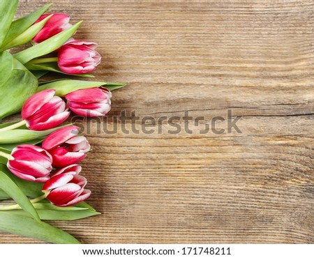 Bouquet of pink tulips on wooden background. Copy space - stock photo