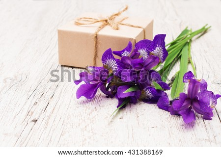 bouquet of purple flowers irises and gift on a light wooden background (shallow depth of field) - stock photo
