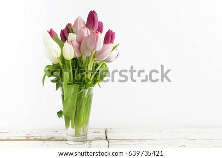 Bouquet of purple tulips on white wood