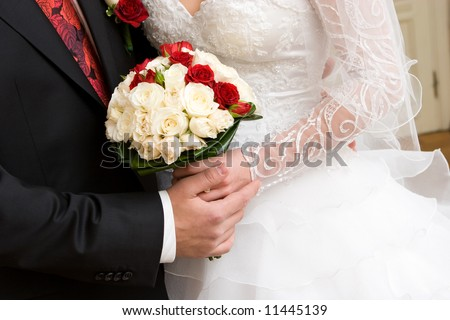 bouquet of red and white roses in the hands of newly married couple