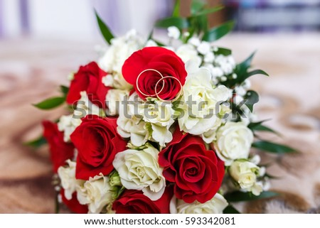 bouquet of red and white roses with wedding rings