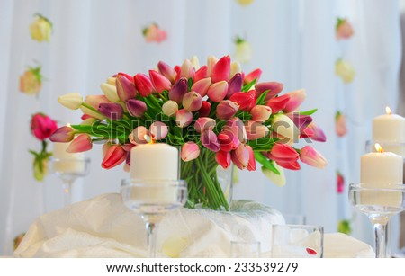Bouquet of red and yellow tulips on a festive table. Wedding decoration.Burning candles stand. Hanging rosebuds. - stock photo