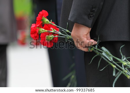 Bouquet of red carnations in man hand at Victory Day celebrations; focus on flower - stock photo