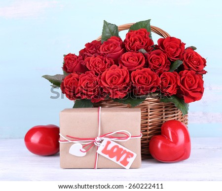 Bouquet of red roses in basket with present box on wooden background - stock photo