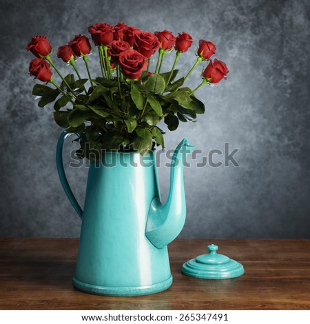 Bouquet of red roses in retro turquoise coffee pot on wooden surface behind grey wall background   - stock photo