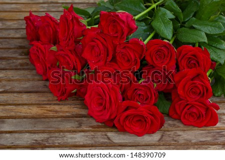 bouquet of red roses in water droplets on wooden table - stock photo