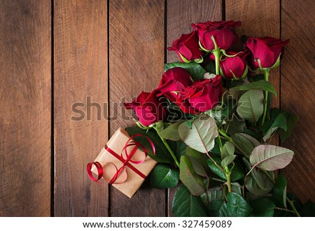 Bouquet of red roses on a dark wooden background. Top view - stock photo