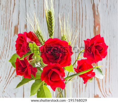 Bouquet of red roses with green ears of wheat on a background of old painted board - stock photo
