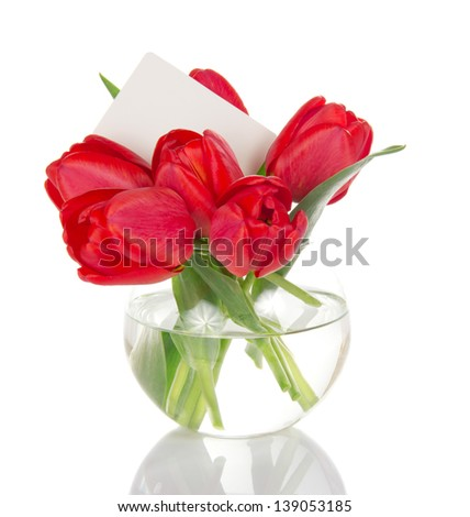 Bouquet of red tulips in a round vase and the empty card, isolated on white - stock photo