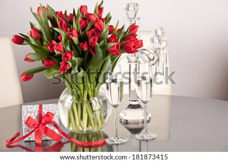 Bouquet of red tulips on the table and glasses with champagne, gift box. Fresh spring flowers