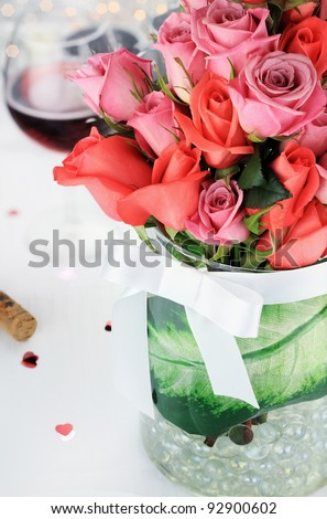 Bouquet of roses against a romantic table setting. Selective focus on roses blossoms with blur on lower portion of image.