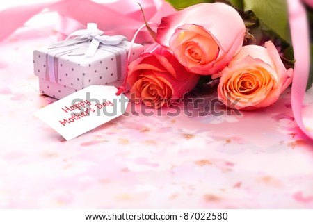 Bouquet of roses and gift box with a mother's day card