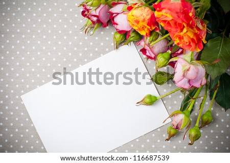 Bouquet of roses and white cardboard on a gray linen fabric closeup