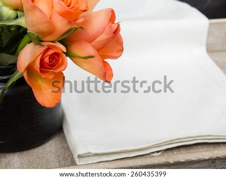 bouquet of roses and  white napkin on wooden tray