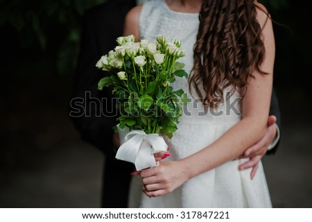 bouquet of roses at hand of couple - stock photo