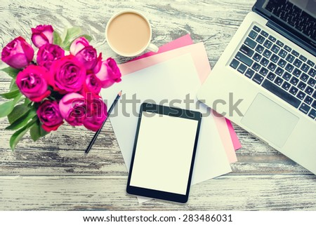 Bouquet of roses, cup of coffee, female hands with tablet and laptop on old wooden table. Top view. Toned image - stock photo