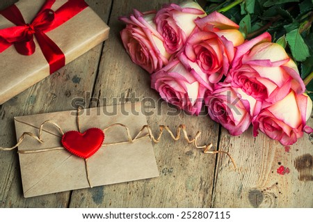 Bouquet of roses , envelope and gift box on  wooden background. - stock photo