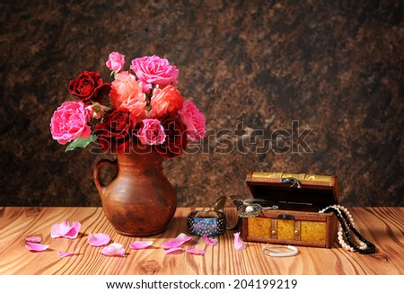 Bouquet of roses in a ceramic vases and jewelry on the table - stock photo