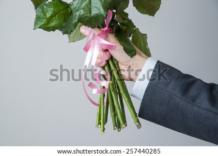Bouquet of roses in a male hands on a gray background - stock photo