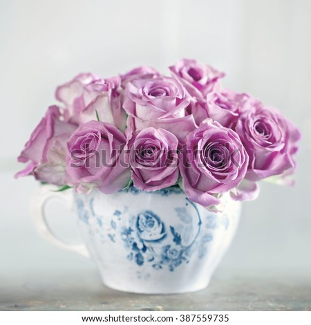 Bouquet of roses in an old cup on vintage wooden background