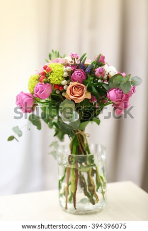 Bouquet of roses in jar on the table - stock photo